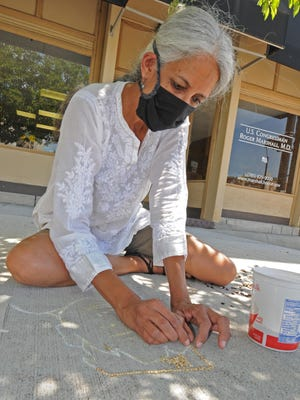 """Salina artist Priti Cox starts on her second """"Seeds for Justice"""" sidewalk art display made of indigenous seeds near U.S. Rep. Roger Marshall's Salina office, 200 E. Iron Ave., which shows a portrait of a black man named Tony McDade who was a victim of police violence in Tallahassee, Fla., last week. """"I used a combination of soybeans, wheat, sorghum, and sunflower seeds as we are the bread basket of world,"""" Cox said."""