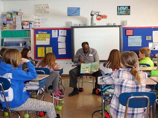 Corning Inc. employee Harry Robinson reads to Big Flats Elementary students as part of the African-American Read-in program.