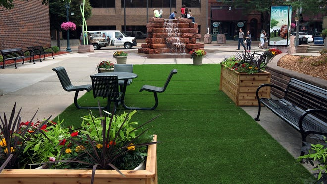 A pop-up park on Phillips Avenue Plaza features fake grass and planters made specifically for the pop-up park, potted flowers and benches.