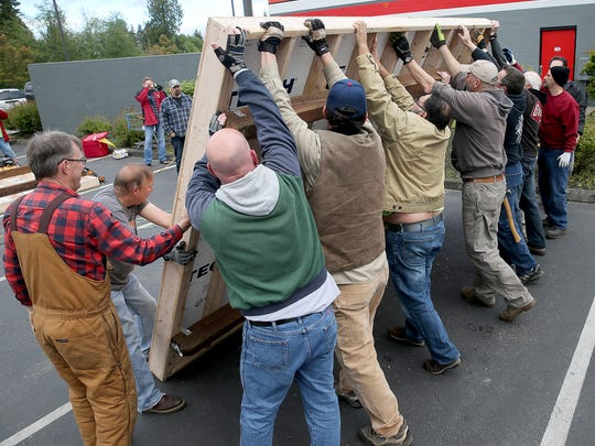 Community volunteers lift up the floor to a tiny cottage being built in Port Orchard on Saturday. Three prototype buildings were being built to demonstrate to the community what such homes would look like.