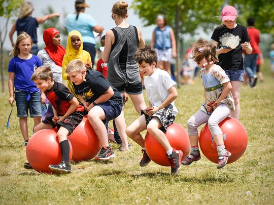 Students race on hippity hop balls during an end of the school year carnival at Kennedy Community School Wednesday, June 7, in St. Joseph.