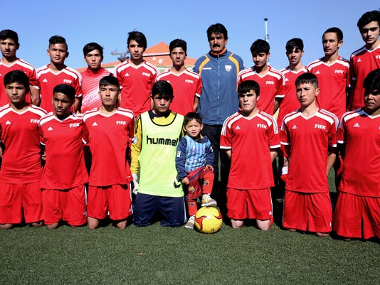 Martaza Ahmadi, a five-year-old Afghan Lionel Messi fan, center, poses for a photo with a football team, at the Afghan Football Federation Stadium in Kabul, Afghanistan, Tuesday, Feb. 2, 2016. The Afghan Football Federation plans to set up a meeting between  Messi and Ahmadi who became an Internet sensation when photos circulated of him wearing an improvised Messi shirt made from a plastic bag. (AP Photo/Rahmat Gul)