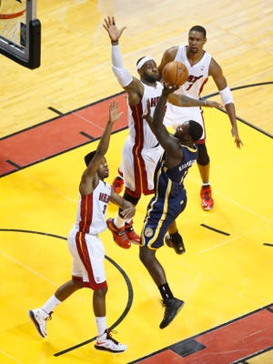 Pacers guard Lance Stephenson tries to shoot over Heat guard Norris Cole (30) and forward LeBron James during Game 4 of the Eastern Conference Finals.