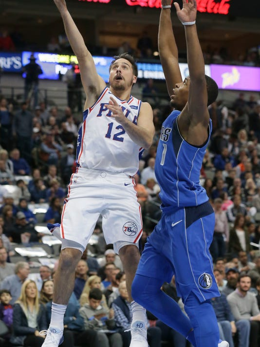 Philadelphia 76ers guard T.J. McConnell (12) shoots against Dallas Mavericks guard Dennis Smith Jr. (1) during the first half of an NBA basketball game in Dallas, Saturday, Oct. 28, 2017. (AP Photo/LM Otero)