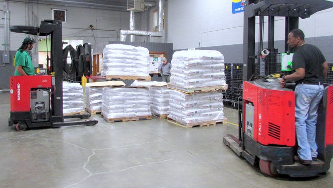 Employees of the Food Bank of the Southern Tier on Monday unload some of the 40,000 pounds of pet food donated by PetSmart.