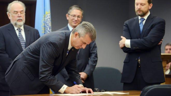 Judge Mark Salter signs a memorandum of understanding Monday at an event marking the start of the Minnehaha County Veterans Treatment Court at the Minnehaha County Courthouse, Dec. 14, 2015.