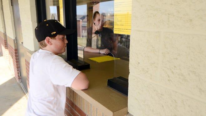 Grant Odom, 12, orders nachos during an Oak Grove home baseball game on Thursday.