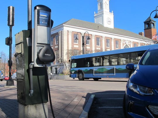 A public bus passes an electric-car charging station on Wednesday at Church and Main streets in Burlington.