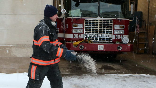 Yonkers firefighter Danny Ortiz spreads salt along the apron of Fire Station 4 on Radford Street in Yonkers, during the snowstorm March 14, 2017.