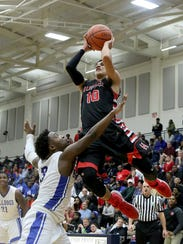 Hughes' Giovanni Santiago (10) shoots over Woodward's Demontez Cooper during their regional semifinal game, Thursday, March 15, 2018.