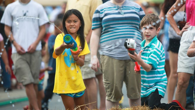 Arwen Imfeld; age 9, at left, and Jayden Mills; age 8, squirt water at participants in a buggy race during the resurrected LAAFF festival on Sunday afternoon.  LAAFF; which stands for the Lexington Avenue Arts and Fun Festival, featured live music, street performers, food trucks, vendors of all types, kids activities and more. -Colby Rabon (colbyrabon@gmail.com) August 31, 2014