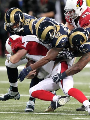 Arizona Cardinals quarterback Drew Stanton (5) is sacked bythe  St. Louis Rams' Aaron Donald (99), Alec Ogletree (52) and Eugene Sims (97) during the second half on Thursday, Dec. 11, 2014, in St. Louis.