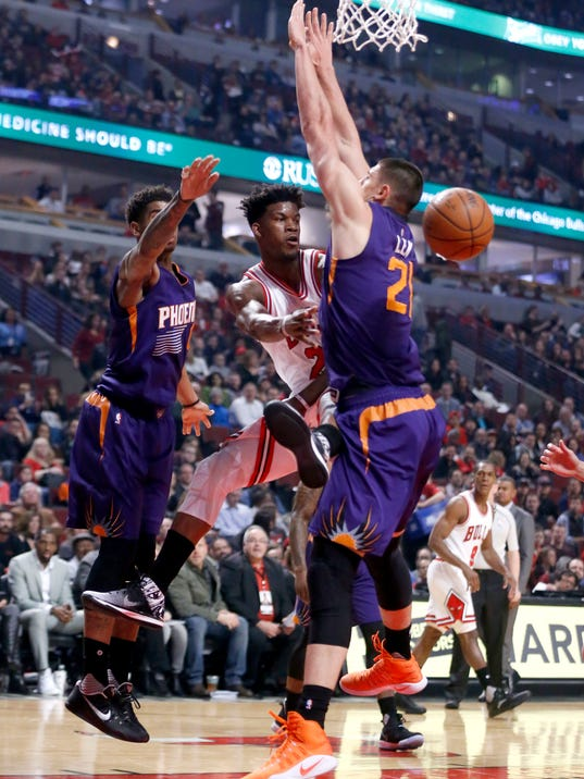 Chicago Bulls' Jimmy Butler, center, passes between Phoenix Suns' Marquese Chriss, left, and Alex Len during the first half of an NBA basketball game Friday, Feb. 24, 2017, in Chicago. (AP Photo/Charles Rex Arbogast)