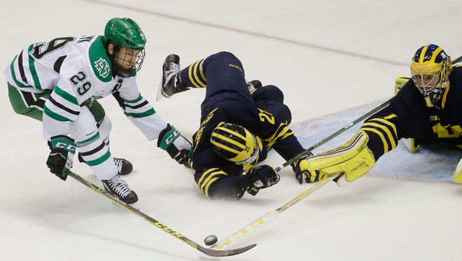 Michigan goalie Steve Racine reaches for the puck against North Dakota's Bryn Chyzyk as Michigan's Nolan De Jong falls during the second period.