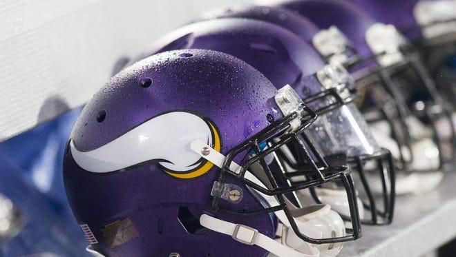 Minnesota Vikings helmets on the sideline bench.