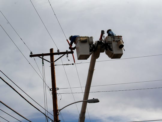 A Farmington Electric Utility System employee works to restore power Friday near Butler Avenue and 18th Street in Farmington after the line was hit by lightning.