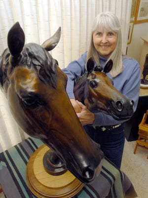 "Dawn Weimer stands with an early sculpture, ""Show's Promise,"" at her home Monday April 13, 2009."
