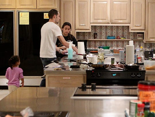 A family makes dinner in the kitchen of the Ronald
