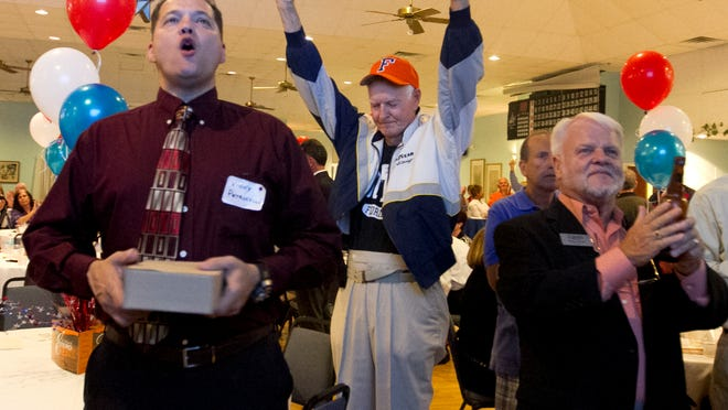 Vinny Petrocelli, left, Tom Myers, center, and Gary Israel cheer after it was announced that the incorporation of Estero was approved by voters on Tuesday night, November 4, 2014.