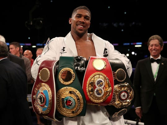 Anthony Joshua celebrates with his belts after victory over Joseph Parker to become the WBA, IBF and WBO heavyweight champion at the Principality Stadium in Cardiff, Wales, Saturday March 31, 2018.  (Nick Potts/PA via AP)