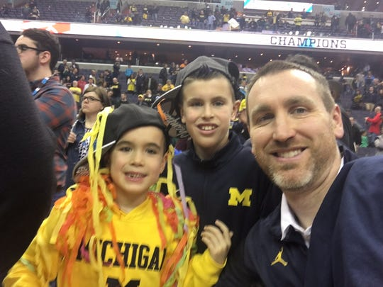 Jon Sanderson with his sons Joshua, 6, and Jonathan, 9, after Michigan won the Big Ten Tournament championship.