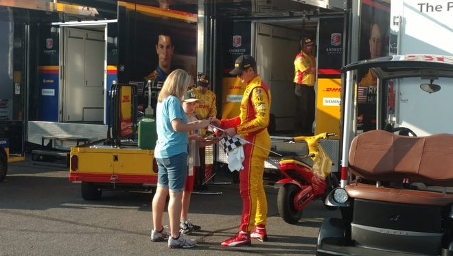 After a long day, an banged-up and exhausted Ryan Hunter-Reay sign an autograph for a fan Sunday at Pocono Raceway.