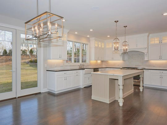 The kitchen features all white cabinets with designer