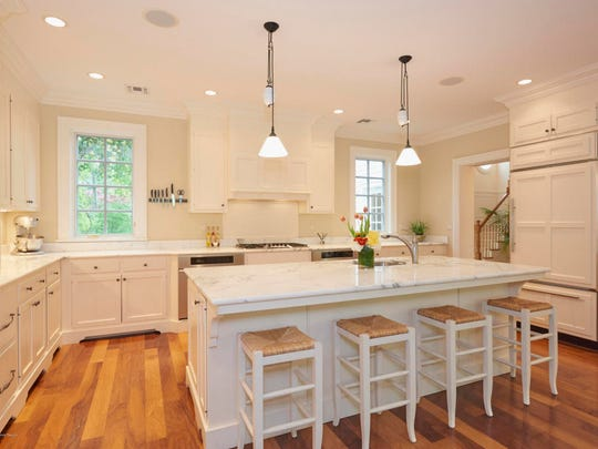 The kitchen offers custom cabinetry with recessed lighting.