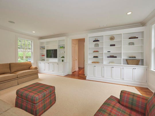 The family room features wall to wall carpet and a set of custom bookshelves.