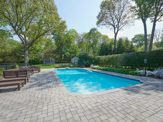 In the backyard, features a heated in-ground pool and playground.