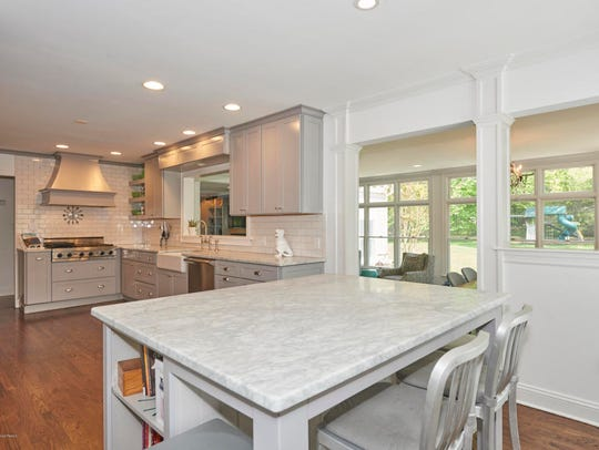 The kitchen features a marble center island, recessed lighting, and stainless steel appliances.