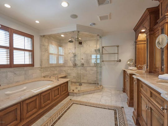 The Master bathroom features a custom built-in with his and her sinks with a jetted tub and tile flooring.