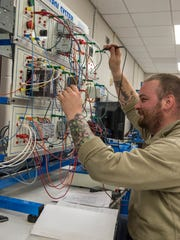 James Messenger, 30, works on an electrical panel at the Regional Manufacturing Technology Center.