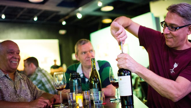 Andrew Magitz, right, opens a bottle of wine with Julio Alvarado, left, and Ed Kelety, center, at The Nash jazz club in Phoenix, AZ, on Wednesday, June 17, 2015. The club features a BYOB drinking policy and sits across the street from Roosevelt Community Church.