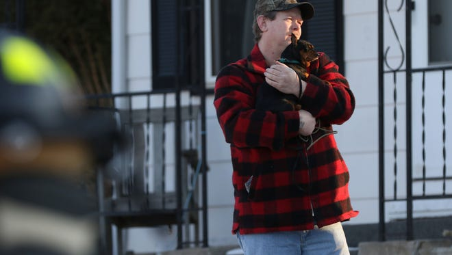 Pete Kizer, a tenant at 306 W. Cleveland St. in Marshfield, clutches his 4-year-old pinscher named Razzi. Kizer brought the dog outside as firefighters looked for the source of smoke coming from the residence shortly after 4 p.m. on Monday, Feb. 1, 2016.