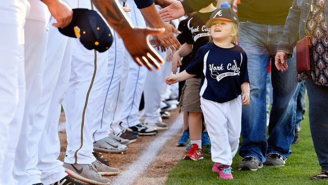 York Little League player Marley Miller, 4, greets York Revolution players before the Revs' home opener against the Lancaster Barnstormers Thursday, April 26, 2018, at PeoplesBank Park. The Revs open their 12th season as defending champions after winning their third Atlantic League title in 2017.