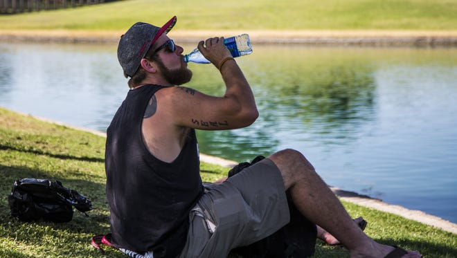 Justin Seal takes a long drink of water in the shade as he finishes fishing at Dobson Ranch Park in Chandler on June 5, 2017.