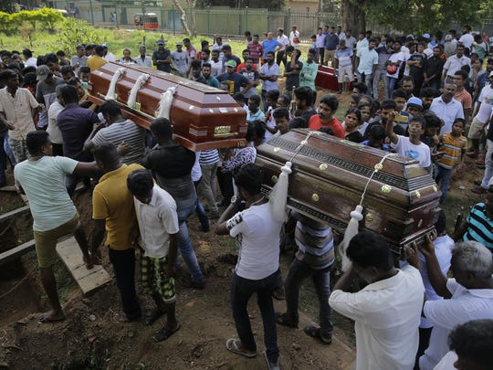 Sri Lankans carry the coffins with the remains of Berington Joseph, left, and Burlington Bevon, right, who were killed in the Easter Sunday bombings in Colombo, Sri Lanka.