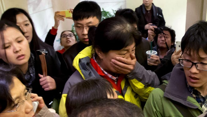 A woman is surrounded by media as she arrives at a hotel prepared for relatives or friends of passengers aboard missing Malaysian Airlines Flight MH370 in Beijing on Saturday.