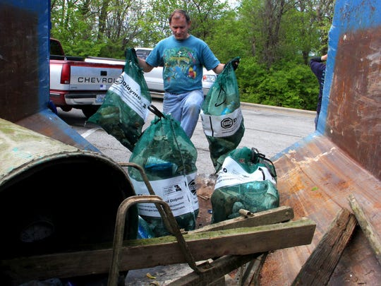 Volunteer Mark Lane pitches trash into a metal bin during a past l Joe Kleiber Memorial Earth Day Celebration and cleanup at Lake Springfield. .