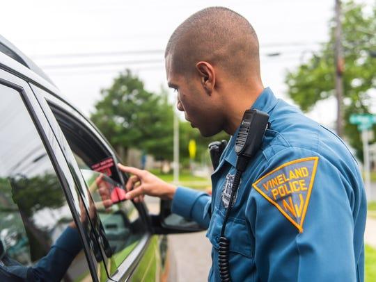 Vineland police officer AJ Santiago inspects a window