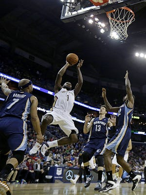 New Orleans Pelicans point guard Tyreke Evans (1) shoots between Memphis Grizzlies point guard Jerryd Bayless (7), small forward Mike Miller (13) and power forward Ed Davis (32) in the first half of an NBA basketball game in New Orleans, Friday, Dec. 13, 2013. (AP Photo/Gerald Herbert)