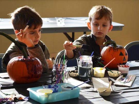 Nikola Pepovski, 7, and Filip Pepovski, 6, both of Mays Landing paint their pumpkins.