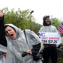 Dez Harding, left, Ashley Dixon, center, Tiyara Locklear, right, yell during a protest for better wages for fast food workers along Hendersonville Road in Asheville in April.
