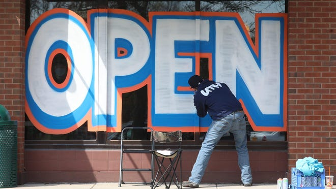 A large open sign is painted in the window of the Subway restaurant in Twelve Corners in Brighton on Tuesday, April 28, 2020.  The worker, who was painting the sign for a friend, did not want to be identified.
