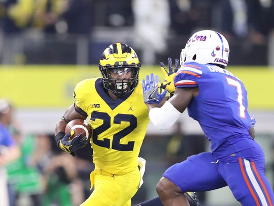 Michigan's Karan Higdon battles Florida's Duke Dawson