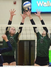 Novi's Erin O'Leary (14) and Emmy Robinson (4) team up to slow down a spike attempt by Central's Sophie Colvin.