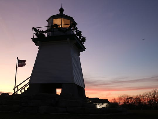 As the sun goes down, the Port Clinton Lighthouse continues