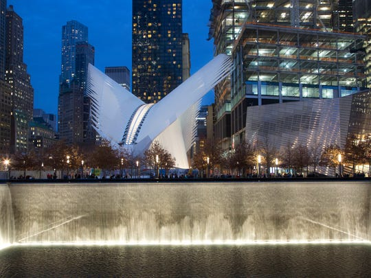 FILE - This Dec. 11, 2015 file photo shows The World Trade Center transportation hub, center, overlooking the September 11 Memorial north reflecting pool in New York. The 9/11 memorial park is a must for anyone visiting New York City. It's one of the city's best free attractions but more important, it's a powerful symbol of the city's resilience and a tribute to those who perished on Sept. 11, 2001.