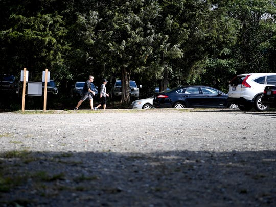 A pair walk past a gravel parking lot on Banks Avenue